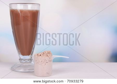 Whey protein powder and chocolate protein shake on table on bright background