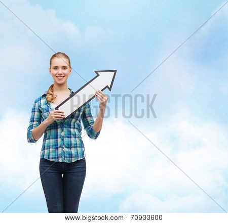 happiness, direction and people concept - smiling young woman arrow poiting up over blue sky background