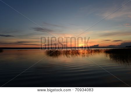 Boundless Expanse Of Water Of The Lake To The Setting Sun At Sunset With The Sun Fading Glow In The