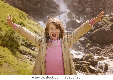 Girl With Open Arms Standing In Front Of Waterfall