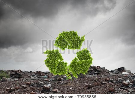 Conceptual image with recycle green sign growing on ruins