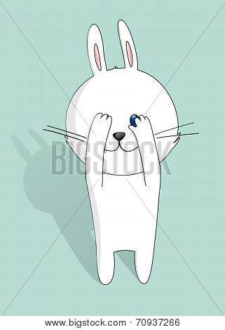 Little white bunny peeking through hand with one eye