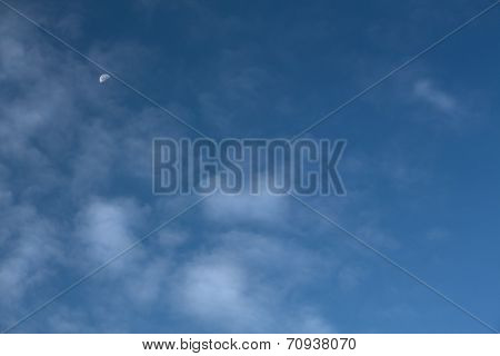 Blue Sky With Half Moon And Wispy Clouds