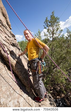 Senior Man Starting Rock Climb In Colorado