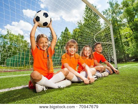 Children sit together on field with football