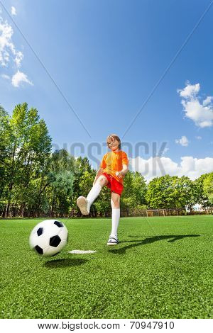 Boy kicking football with one leg