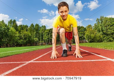 Boy in position to run with arms on the ground