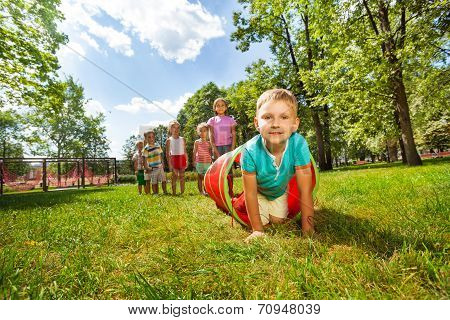 Boy and his friends crawling through the tube