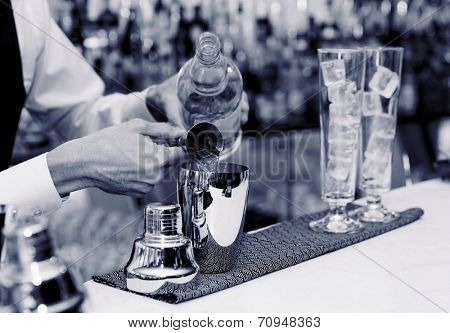 Bartender is pouring liquor in shaker, blue toned