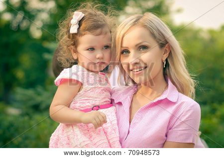 Pretty mother and daughter on the green summer garden