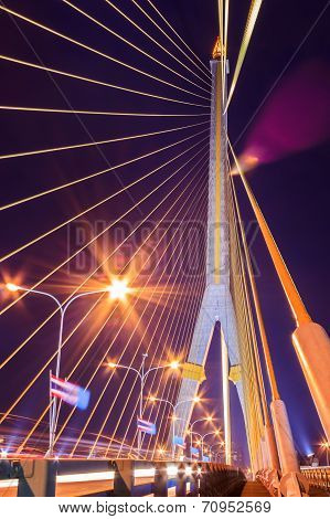 The Rama VIII bridge over river at night in Bangkok Thailand with roadway movement