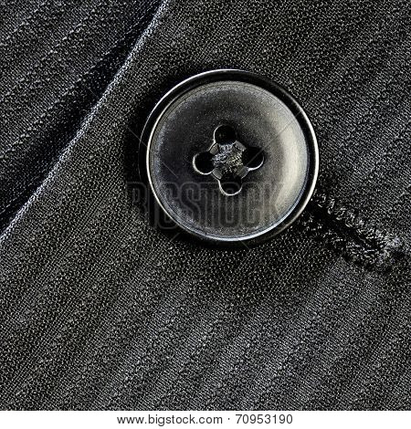 Detail of closeup of suit button on pin stripped cloth