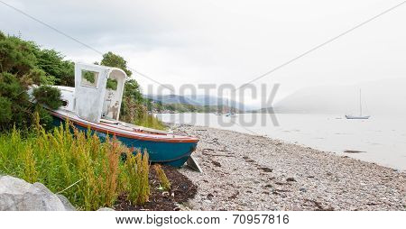 Small Shipwreck At A Loch With Stone Beach