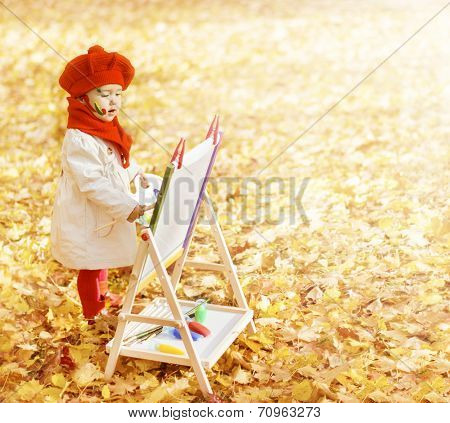 Child In Autumn Park Painting Picture On Easel. Creative Little Kid And Yellow Fall Leaves