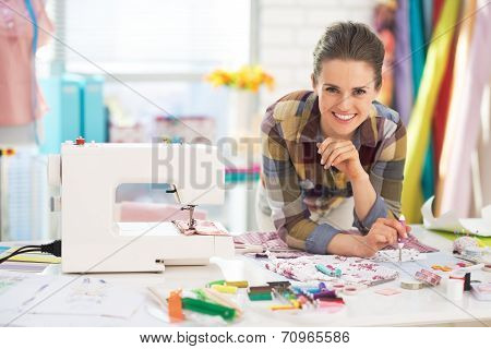 Portrait Of Smiling Tailor Near Sewing Machine