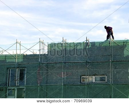 Worker carrying drill on the roof