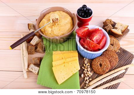 Fondue, tomatoes, olives, biscuits, slices of cheese and rusks on cutting board on napkin on wooden background