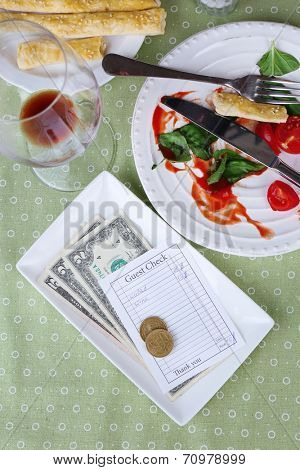 Check and remnants of food and drink on table in restaurant