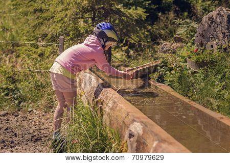 Girl Wearing Bike Helmet Playing In Water Trough