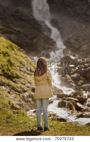 Rear View Of Girl Standing And Admiring Waterfall