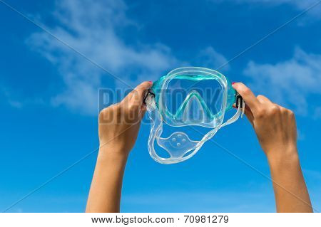 Hand holding snorkel goggles ( mask for diving) against beach and sky