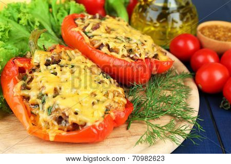 Stuffed red peppers with greens ans vegetables on wooden stand on table close up