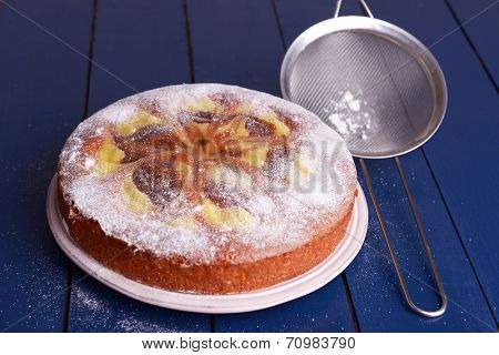 Delicious cake and sieve with powdered sugar on wooden table