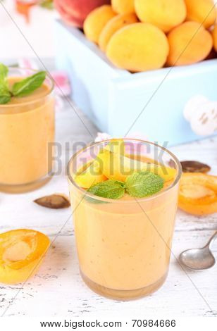 Apricot dessert and apricots in glasses on table close-up