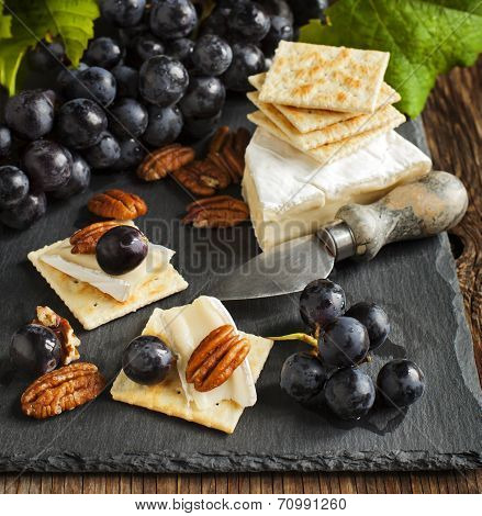 Delicious Cheese Crackers Appetizer With Grapes And Pecans On Cooking Board.