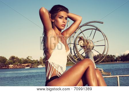 attractive young woman on the bow of a fishing boat sunny summer day on sea