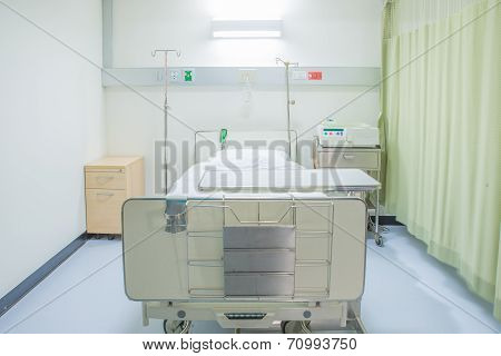 A Hospital Room With Bed And Chair