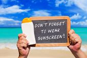 picture of slating  - Human Hands hold a bottle sunscreen and a slate blackboard with text message  - JPG