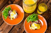image of benediction  - English muffin with bacon egg benedict with hollandaise sauce and arugula salad fresh orange juice - JPG