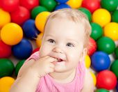 stock photo of infant  - Portrait of a smiling infant sitting among colorful balls - JPG