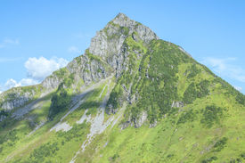 picture of arrowheads  - Rocky rugged Arrowhead Peak near Sitka Alaska with green forested slopes on clear sunny day with blue sky - JPG