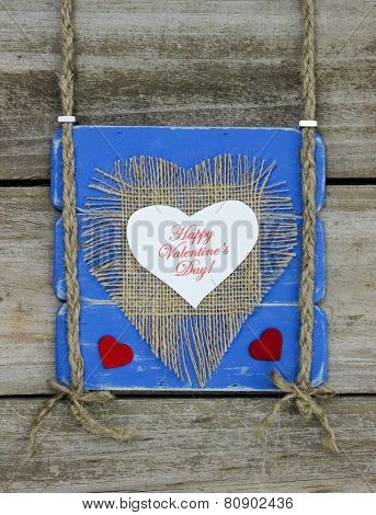 Happy Valentine's Day heart on blue sign hanging on wood fence