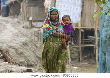 Woman takes care of her baby in Mongla, Bangladesh.