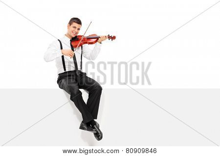 Male violinist playing seated on a blank panel isolated on white background