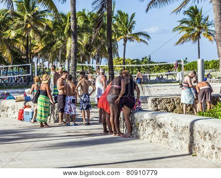 People Walk Along The Promenade At Ocean Drive In South Beach