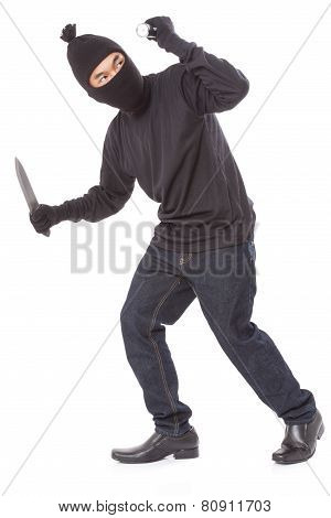 Man in a mask holding flashlight with a knife
