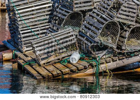 Old wooden lobster traps with buoys and rope on a wharf in Newfoundland, Canada.