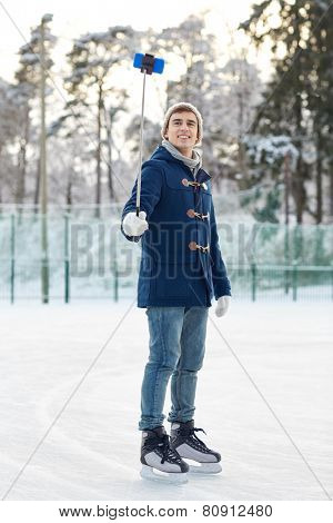people, winter, technology and leisure concept - happy young man taking picture with smartphone selfie stick on ice skating rink outdoors