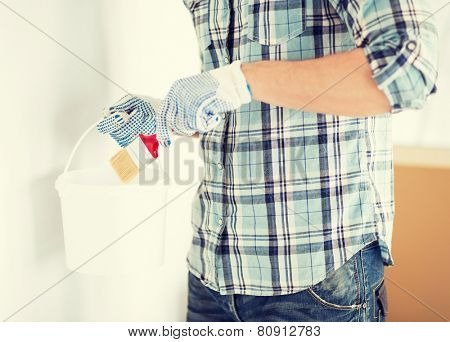 interior design and home renovation concept - man hands with paintbrush and paint pot