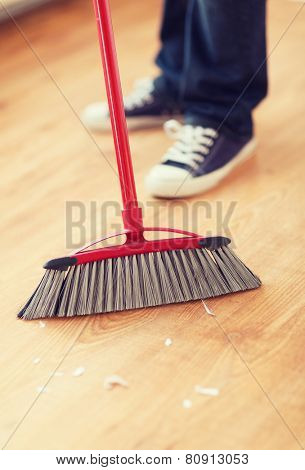 cleaning and home concept - close up of male brooming wooden floor