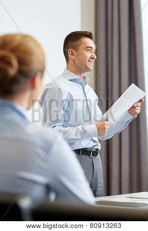 business, people and teamwork concept - smiling businessman holding papers and woman on presentation in office