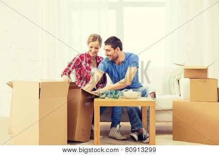 repair, building and home concept - smiling couple unpacking kitchenware