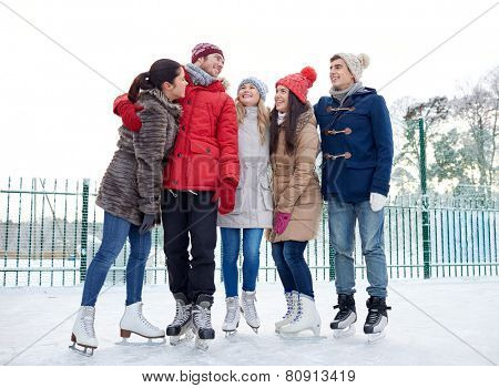 people, winter, friendship, sport and leisure concept - happy friends ice skating and hugging on rink outdoors