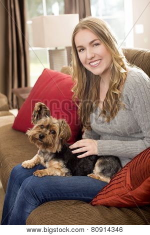 Young woman sitting on a couch with her dog