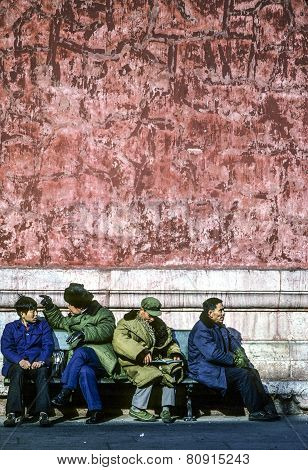 Chinese People In Green And Blue Parka Sit At A Bench In Front Of The Forbidden City In Beijing, Chi
