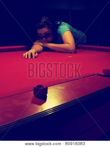 a girl in a bar leaning on a pool table toned with a retro vintage instagram filter effect app or action